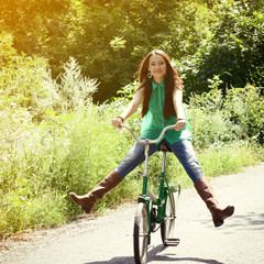Excited young beautiful woman happy riding with retro bicycle, s