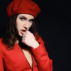 Stylish fashion girl in red suit and beret with, posing at studi