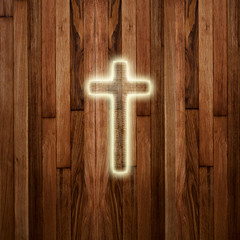 Glowing holy cross on abstract wooden background