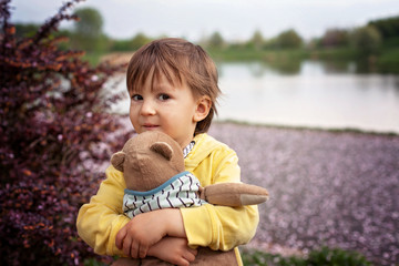 Adorable little boy, holding toy friend in a park