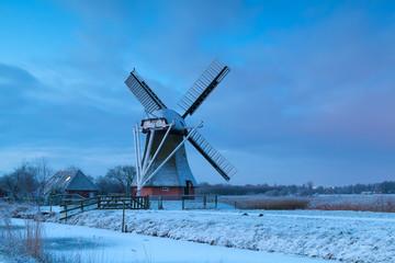 Dutch windmill in snow at sunrise