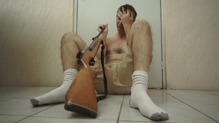 Suicidal Male Sitting on Floor With Rifle