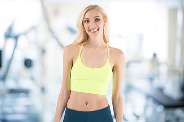 Fitness fit young blond woman standing against sport gym