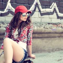 Portrait of beautiful teen girl sitting on skateboard over wall