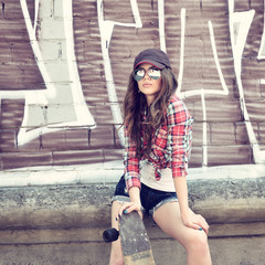Portrait of beautiful teen girl standing on skateboard over wall