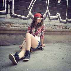 Portrait of beautiful teen girl sitting on skateboard over wall