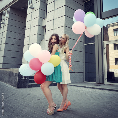 Happy romantic fashion girls with colorful balloons, outdoors. T
