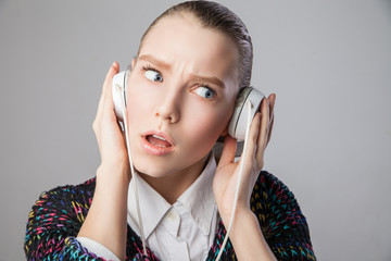 girl with headphones expressing negative emotions