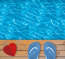 Swimming pool with blue clear water, wooden deck and red paper h
