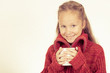 portrait of a cute teen girl in red sweater holding a mug in his
