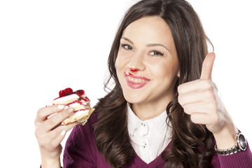 Pretty stained girl eating cake and showing thumbs up