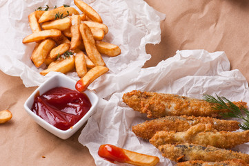 Fish & Chips.Frying sprats  served on the paper. Street food.