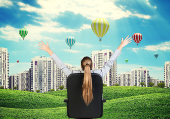 Businesswoman sitting on office chair. Green hills with