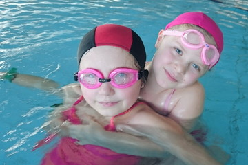 Eight and six years old sisters in the swimming pool.