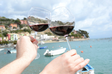 Two wineglasses in the hands against the harbour of Portvenere,