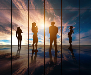 Silhouettes of businesspeople standing against panoramic  window