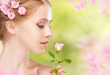 Beauty face of young beautiful woman with pink flowers in her ha