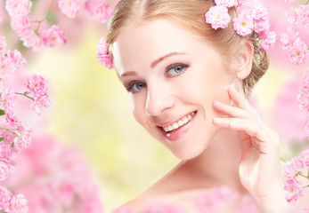 Beauty face of young happy beautiful woman with pink flowers in