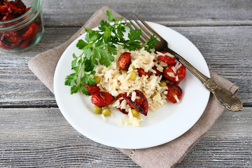 Rice with sun-dried tomatoes and parsley in a white plate