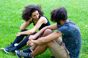 Latin Hipster couple sitting on meadow