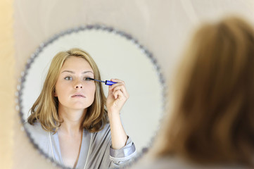 Beautiful young woman doing make-up