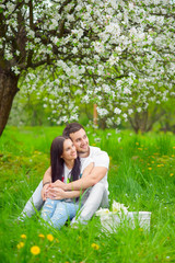 happy young couple in the garden with apple flowers