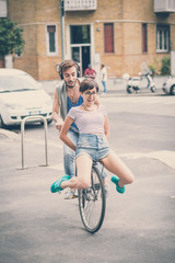 couple of friends young  man and woman riding bike