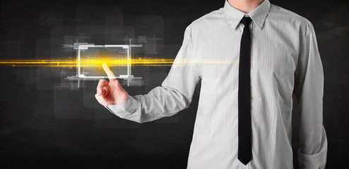 Tech business person touching button with orange light beams con