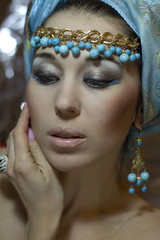 Arab girl in blue turban with gold jewelry.