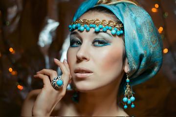 Arab woman in blue turban. Gold jewelry. Fashion makeup.