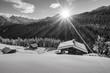 Leinwandbild Motiv Bergsonne über der Schihütte in schwarz weiß