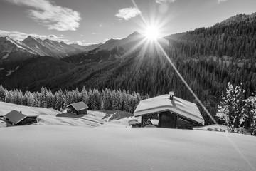 Bergsonne über der Schihütte in schwarz weiß