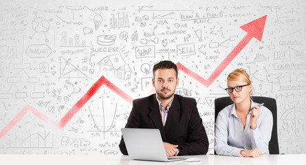 Business man and woman sitting at table with market diagrams