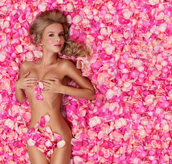 Beautiful slim young woman lying on petals of pink roses. Perfec