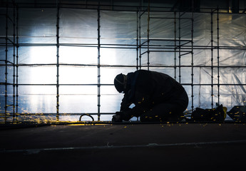 Worker polishes part of steel construction.
