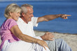 Senior Couple Sitting on Beach Pointing