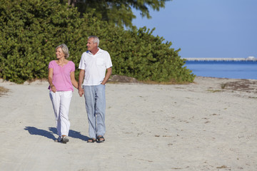 Senior Couple Holding Hands Walking Beach