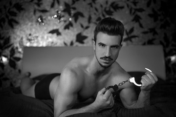 Sexy macho man with handcuffs on bed black and white