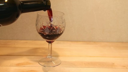 pouring  wine in a wineglass on wooden table