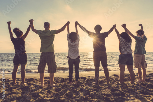 Multiracial group of people with raised arms looking at sunset - 78591094