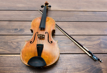 Violin and a bow on a wooden background