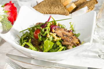 rabbit liver salad with arugula in a restaurant