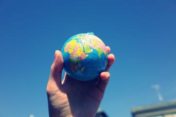 空に向かって持っている地球儀