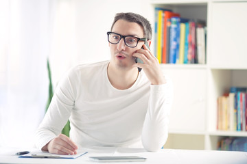 Young man talking on the phone while sitting at the desk