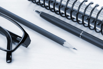 Office table with glasses, notepad and supplies