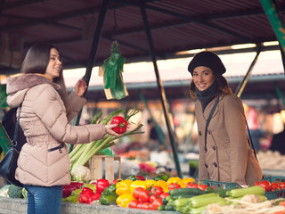 Smiling young woman choosing vegetables at the market place