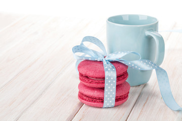 Red macarons with blue ribbon and milk cup