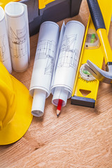 rolled blueprints yellow hardhat red pencil level hammer on wood