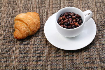 Coffee cup with a croissant and fresh coffee beans on a brown ba