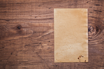 shhet of old paper on vintage wooden board with copyspace for yo